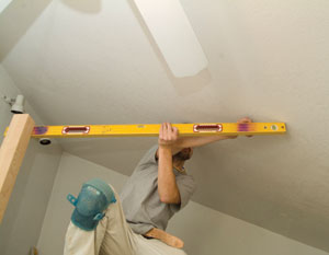 Use a level to transfer the top-of-guardrail mark on the newel post over to the point where the level section of the guardrail intersects the rake of the ceiling.
