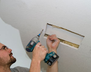 You can hold on to the backer board with one hand, while fastening it to the drywall with the other.