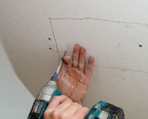 Once the backer board is anchored in place on both sides of the drywall opening, you can put the same piece of drywall back into position.