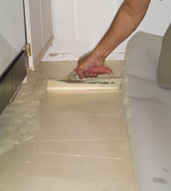 Use a trowel to spread the vinyl adhesive.