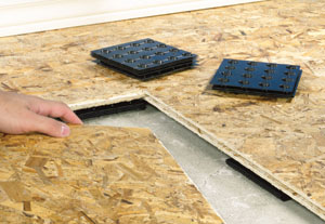 With some insulated subfloor systems, thin plastic shims help to level the subfloor on an uneven slab.