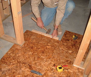 Use a RotoZip or jig saw to make small cuts. Shown here, the installer is fitting a notched panel around a wall.