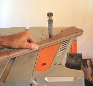 A spindle sander makes easy work of sanding the inside curves of the aprons.