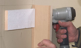 Nail the sides of the mantel legs to the backing.