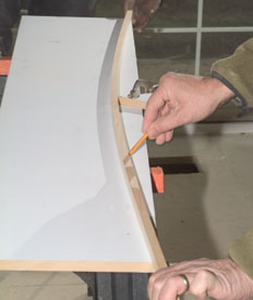 Bend a thin strip of wood over the triangle and to the corners of the face board and trace along the edge. Cut out the arc with a jig saw.