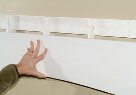 Install the frieze board over the furring strips at the desired elevation. Check the frieze board for level. Nail the frieze board into the furring strips.