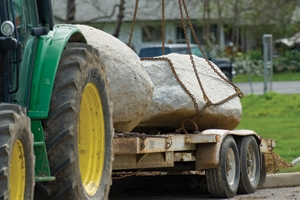 Moving large rocks requires heavy-duty equipment or at least a piece of equipment that you don't care about such as this trailer, which didn't leave the property.