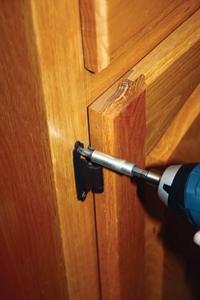 When installing doors, fasten the top hinge first.