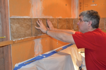 Hal fastened a ledger board above the bathtub, which kept the tile installation level while supporting the vertical load as the mortar set.