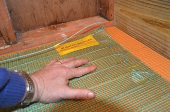 An electric radiant heat system from Warmly Yours provides underfoot heat to the tile floor of the bathroom.