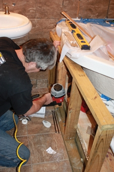 Shown here is Hal erecting the knee-wall that surrounds the tub. The wall will be tiled to provide a transition between the flooring and tub.