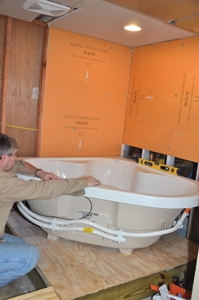 After lifting the tub onto the platform, Hal is checking to ensure the tub is level. Room to work is critical to such a big project. This photo was taken from an adjacent room, and the lack of wall between the rooms made it easy to transport the tub into the space. Erecting the partition wall between the two rooms is the final phase of the project.