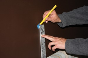 Mark the midpoint on the wall, and map out the picture hook locations and D-ring hangers using this as a reference point.