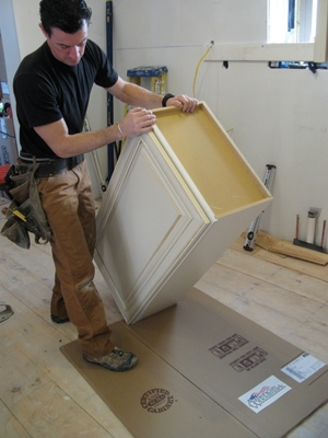 Cabinets often need to be drilled or worked on (in our case for under-cabinet lighting; not the wires in the background). If you ask me, laying them on a jobsite floor is sketchy both for the cabinet and the floor. Cardboard is the perfect substrate. It protects both and costs nothing.