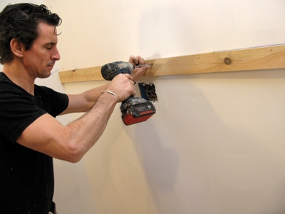 After determining actual cabinet height from the floor's high point, snap the line and install a ledger beneath it. It is important that this is the straightest board in your shop.