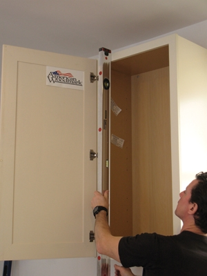 Once the first cabinet is hung, I double-check that it is hanging plumb both front to back and left to right. This cabinet is the control point for the subsequent cabinets that get fastened to it on either side.