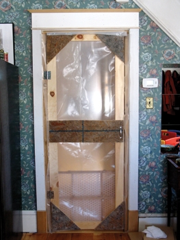 "Here's a site-built ""blast gate"" door. Egress is required to most sites, and I want to keep as much dust behind that door as possible. RRP rules require that you drape an opening, but their recommendation is anemic. An active cold-air return sucking air could easily bypass RRP's draping system and deposit lead dust throughout the home. This blast gate is rugged, opens easily and closes positively. I do need to repair the casing where I fastened it, but that's a small price to pay."
