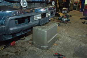 A plastic storage bin makes a good support for the loose bumper.