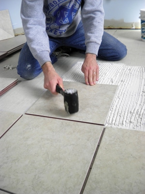 Use a rubber mallet to set the tiles into the mortar bed.