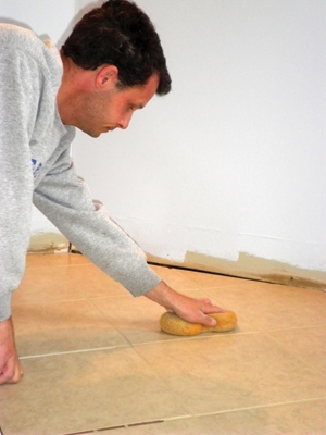 Before moving on to the next section, use a large, wet sponge to wipe the face of each tile, removing the excess mortar before it dries.