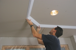Check for proper fit and then attach with adhesive caulk and staples.