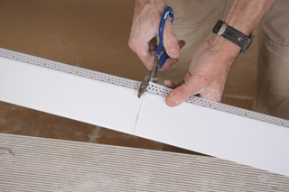 """The angled edge of the tray ceiling will be created with a special vinyl bead called EZ-Tray manufactured by Trim-Tex Drywall Products. The angled edge is 3"""" wide. This angled bead is the piece that bridges the lower ceiling to the raised upper ceiling."""