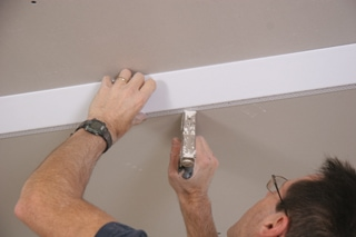 The edge of the bead that attaches to the lower ceiling is stapled in place along the chalk line. This edge will be concealed with joint compound later.