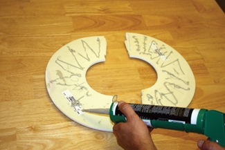 Liberally apply construction adhesive to the rear of the two-piece medallion.