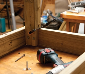 Tap two bolts through the legs, tighten one, and then remove the clamp to drill the third hole.