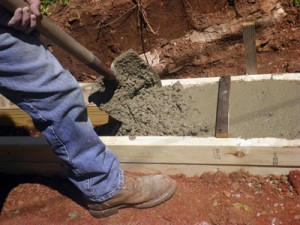 Fill the forms with concrete and level the top with a screed board.