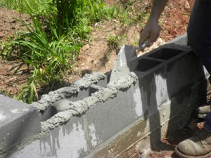 Wet the dried concrete thoroughly, then use a trowel to apply the mortar and block. Remove excess mortar from the joints.