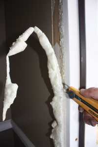 I used spray foam insulation to help weatherproof the door and cut away the excess with a razor. Conceal the gap with new interior casing trim.