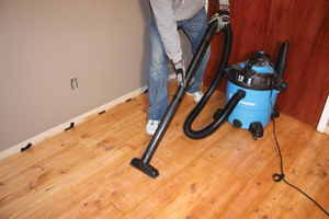 Dust is the enemy of a nice finish. Vacuum all dust and debris from the floor prior to recoating.