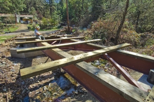 Mike positioned the first five deck boards, which were the longer ones, and attached them to the beam stringers.