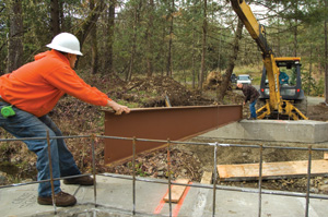 Ford enlisted the help of an excavator equipped with a backhoe to maneuver the I-beams into position.