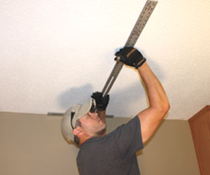 Use a T-square to mark the ceiling joists near the location of your temporary brace wall.