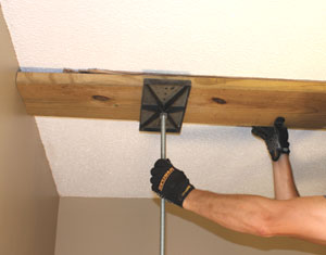 A T-Jak is a helpful tool to support the top plate while you install the studs.