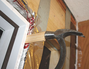 Once the hinge side is plumb and fastened securely, do the same to the latch side. Install wood shims for a snug and plumb fit. After the door is fastened in place you can cut away the extra shim material with a utility knife.