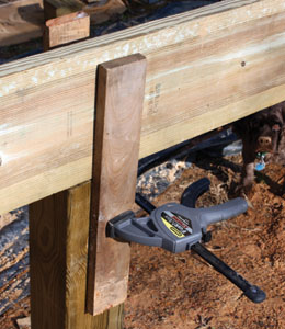 I temporarily clamped on a couple of scrap boards to hold the beam on top of the posts while fastening the connections.
