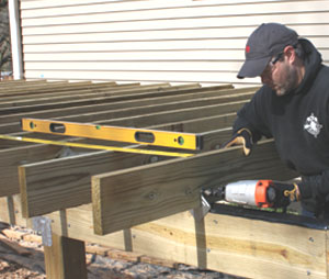 After the joists are installed, add diagonal bracing between the posts and joists to stabilize the deck. Use a recip saw to cut the bracing flush with the tops of the joists.