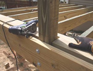 I used a jigsaw to notch the first row of decking to fit around the posts, then completed the walking surface using treated 2x6's as deck boards.