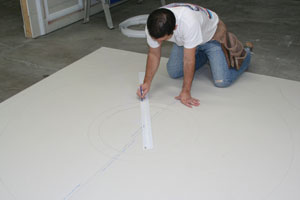 "Utilizing a different design, this installer is drawing a ""wagon wheel"" ceiling detail over two sheets of 5/8"" drywall before he cuts it out."