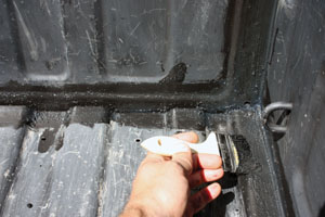 Begin application along the edges and inside corners of the truck bed.
