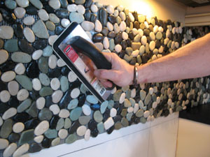 Once adhered, make a permanent connection between the adhesive mat and the tile by pressing in the tiles with a sponge float.