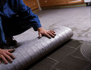 Roll the heating mat into place. The product shown is one of the solid heating mats available from Nuheat.