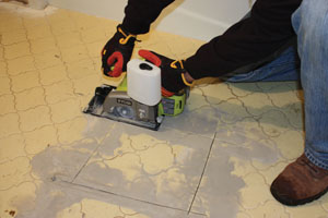 I opened the tile floor by cutting a square with an 18V Ryobi wet saw.
