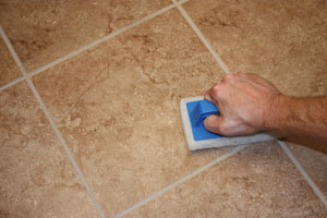 As you apply the grout, use a scrub pad, sponge and clean bucket of water to remove excess grout as you go.