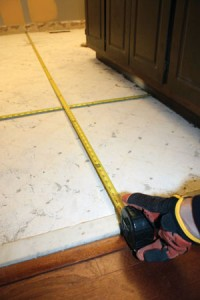 When laying out a tile floor, center the grid to eliminate small, fractional tiles at the perimeter of the floor.