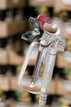 The spray gun, which remains attached to the hose, creates a consistent spray pattern when the nozzle is clean and not overly worn. Abrasive components in the paint eventually wear larger openings in the nozzle with extended use. If the spray nozzle is creating heavy lines in the spray pattern, the nozzle probably needs to be replaced.
