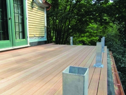 To prevent penetrating the roof membrane, the deck's rail system was designed with post sleeve supports, which fasten onto the decking and into built-up blocking in the joist bay.